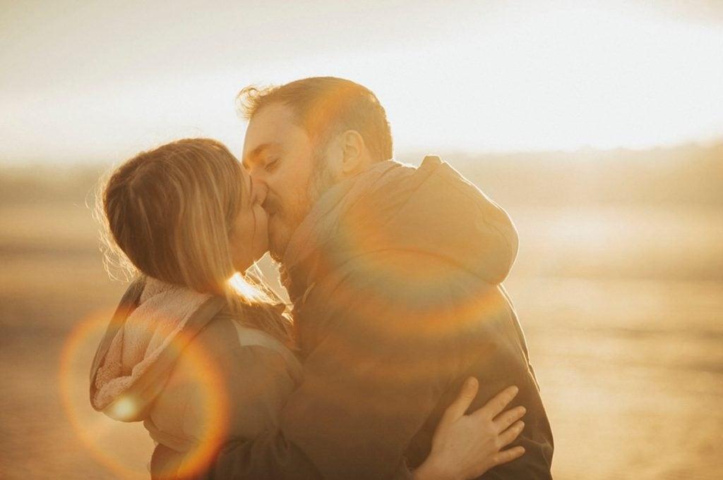 Un gentil couple s'embrasse sur une plage avec des effets d'arc-en-ciel
